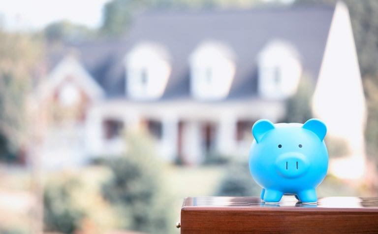 Blue piggy bank in focus in front of blurry home