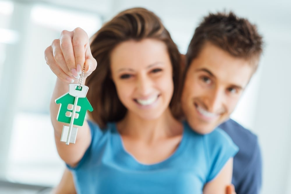 Smiling young couple holding up the key of their first house