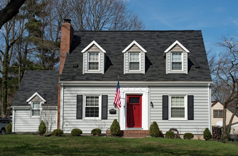 American home with three dormers, red door, and American flag