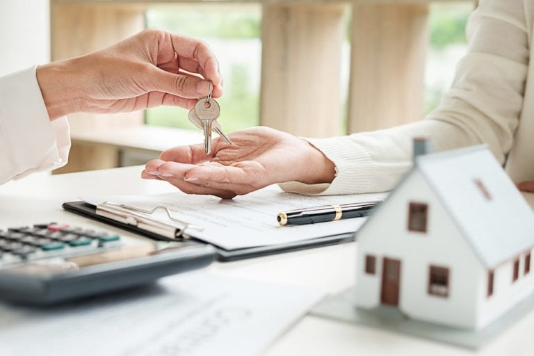 Close-up of person giving another person keys atop desk with a calculator, papers, and a small house model