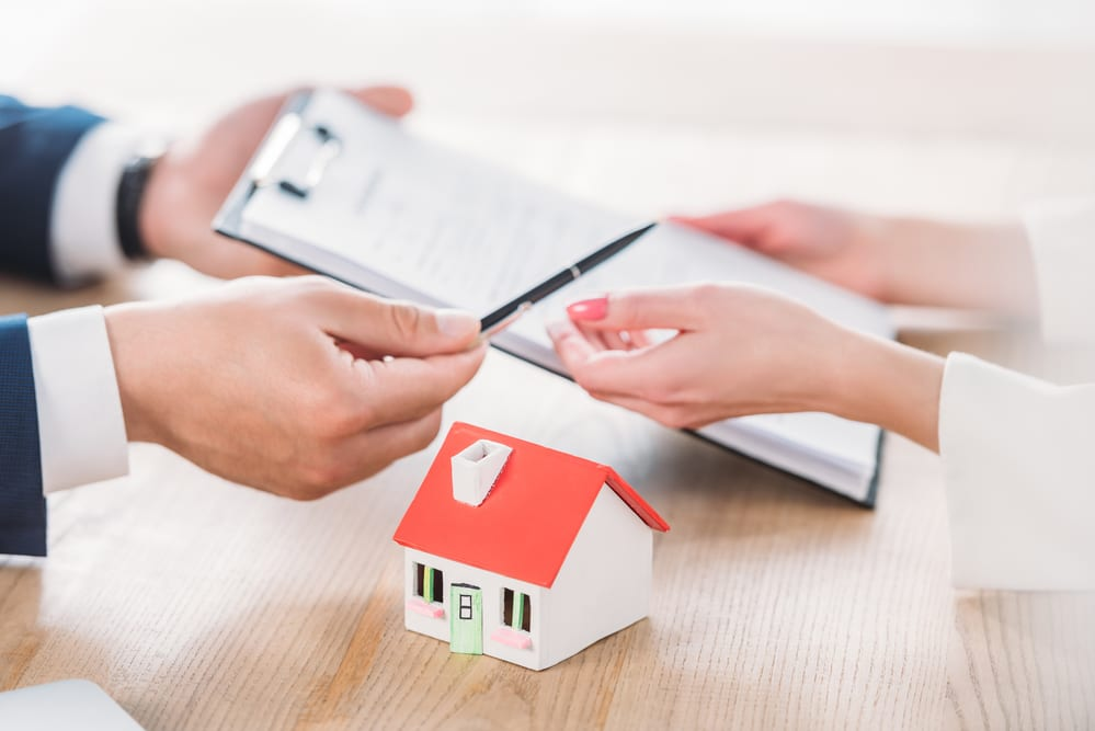 Male hands holding out papers and pen to female hands, small house model